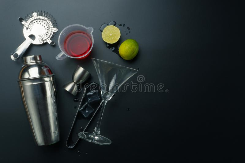 Cosmopolitan cocktail ingredients with bar equipments. Stainless steel cocktail shaker and jigger, cocktail glass with strainer, the lemons and a measuring cup royalty free stock images