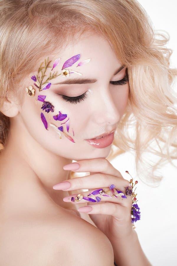 Cosmrtics et manucure Portrait en gros plan de femme attirante avec les fleurs sèches sur son visage, couleur en pastel de concep photographie stock libre de droits