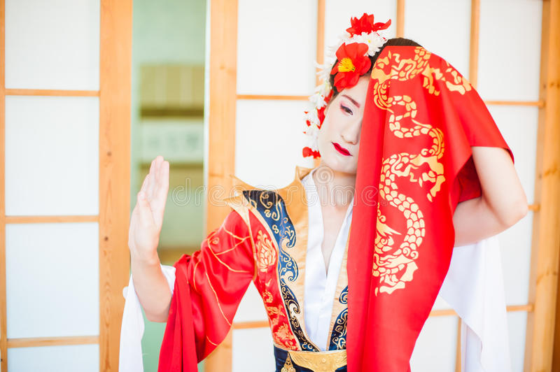 Cosplay. beautiful, modest geisha in a red kimono royalty free stock image