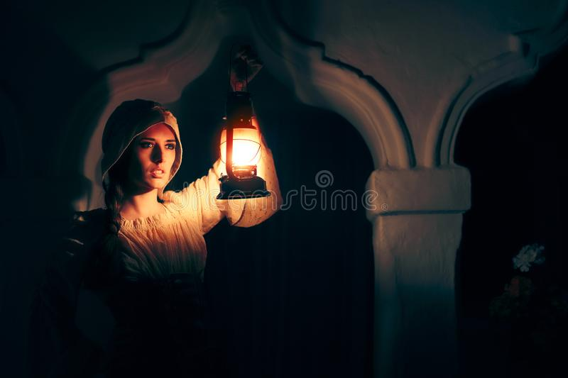 Medieval Woman with Vintage Lantern Outside at Night stock images