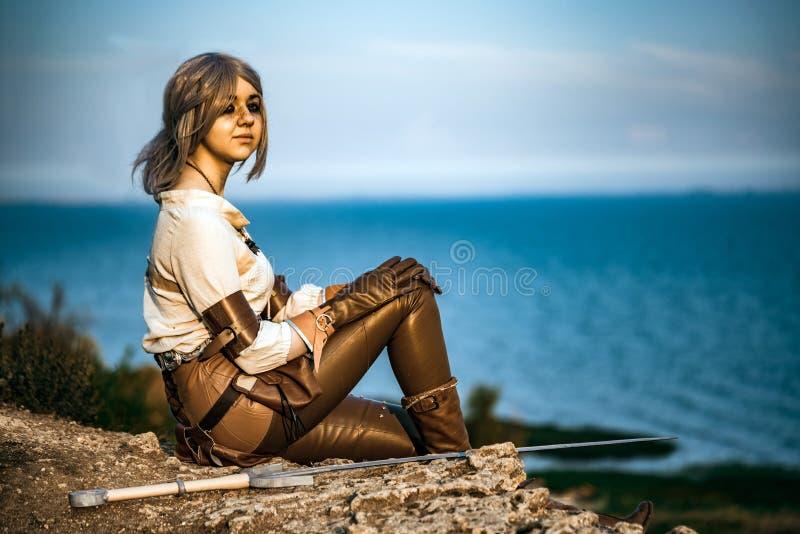 Cosplay härlig Witcher för fantasi flicka på klippan royaltyfria bilder