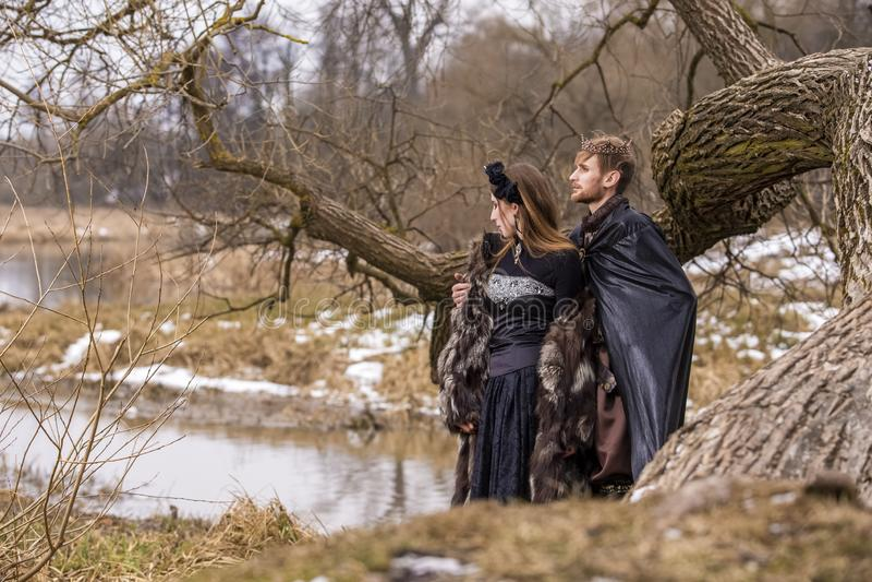 Cosplay idéer Barnet kopplar ihop att posera som prins och prinsessa på forntida bokslut i vårskog arkivfoto