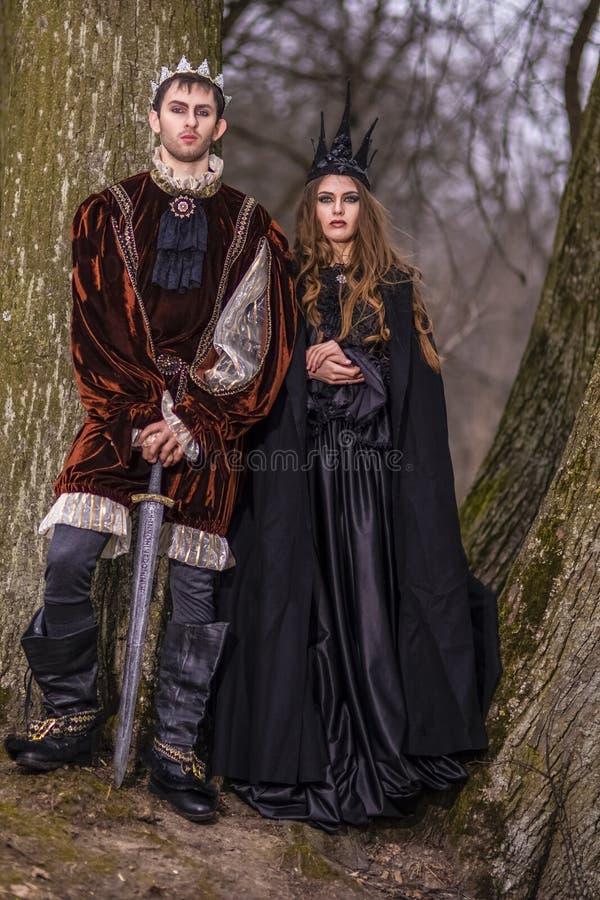 Cosplay idéer Caucasian par som konung och drottning i medeltida dräkt för päls med kronor som tillsammans poserar utomhus- arkivbilder
