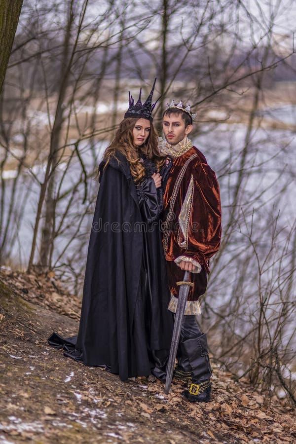 Cosplay idéer Caucasian par som konung och drottning i medeltida dräkt för päls med kronor som tillsammans poserar utomhus- arkivbild