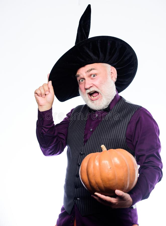 Cosplay outfit. Senior man white beard celebrate Halloween with pumpkin. Wizard costume hat Halloween party. Magician stock photography