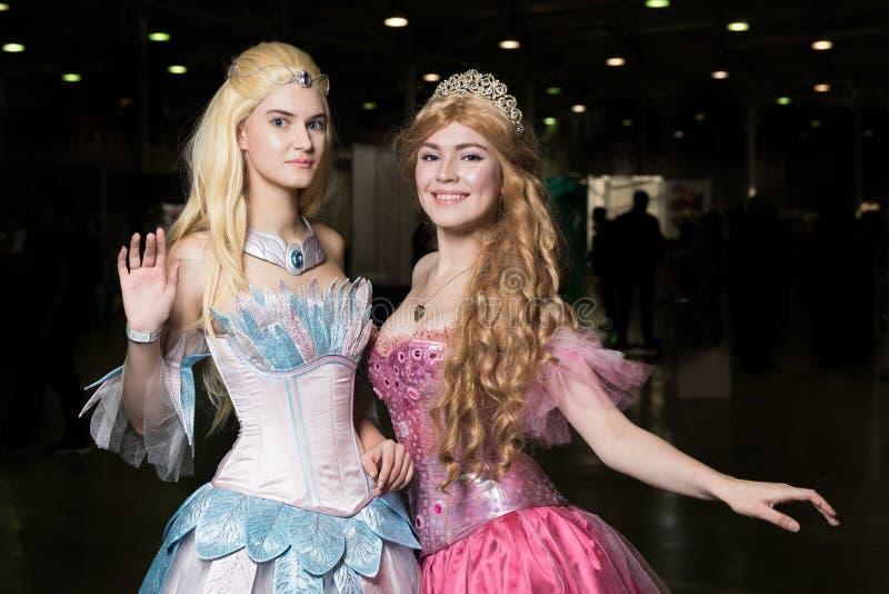 Cosplayer de deux jeunes femmes portant de beaux dres photographie stock libre de droits
