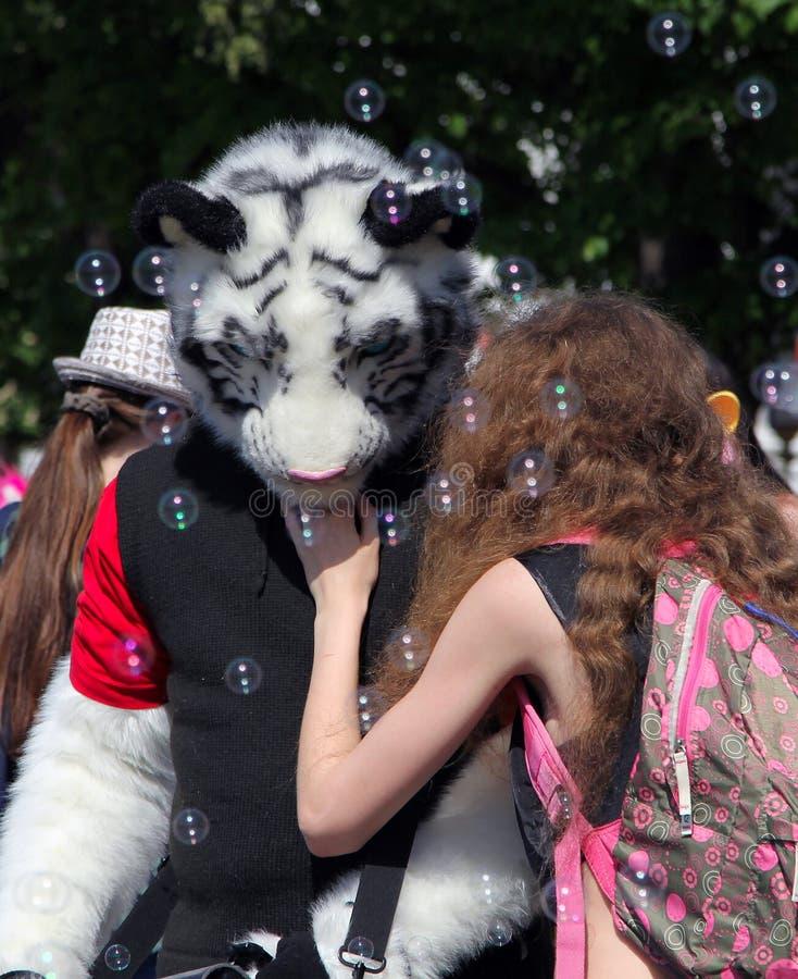 Cosplayer klädde som tiger och en flicka på den Cosplay festivalen royaltyfri bild