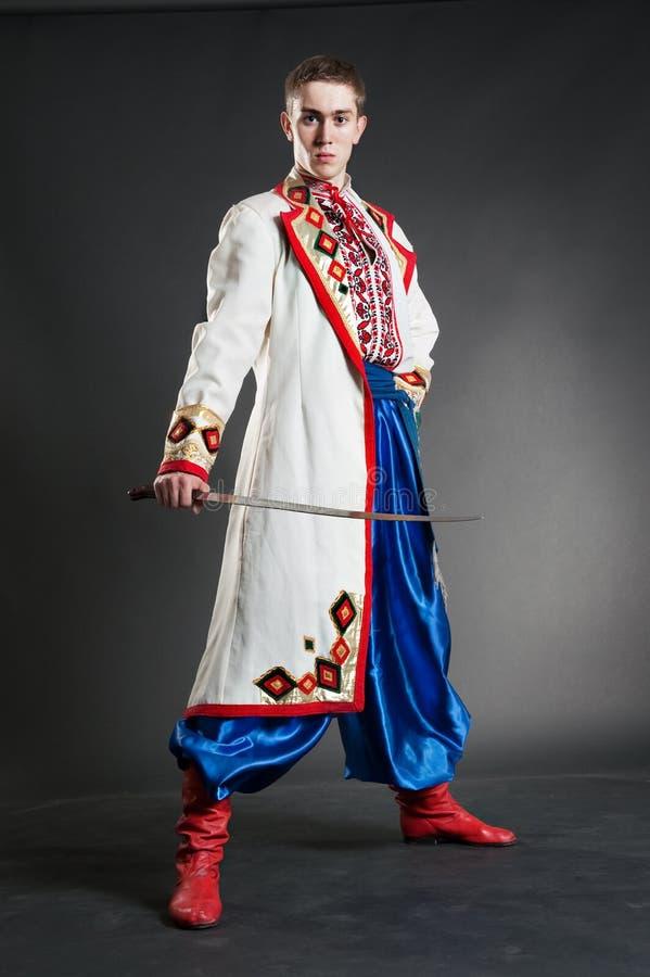 Cossack hermoso joven con el sable foto de archivo