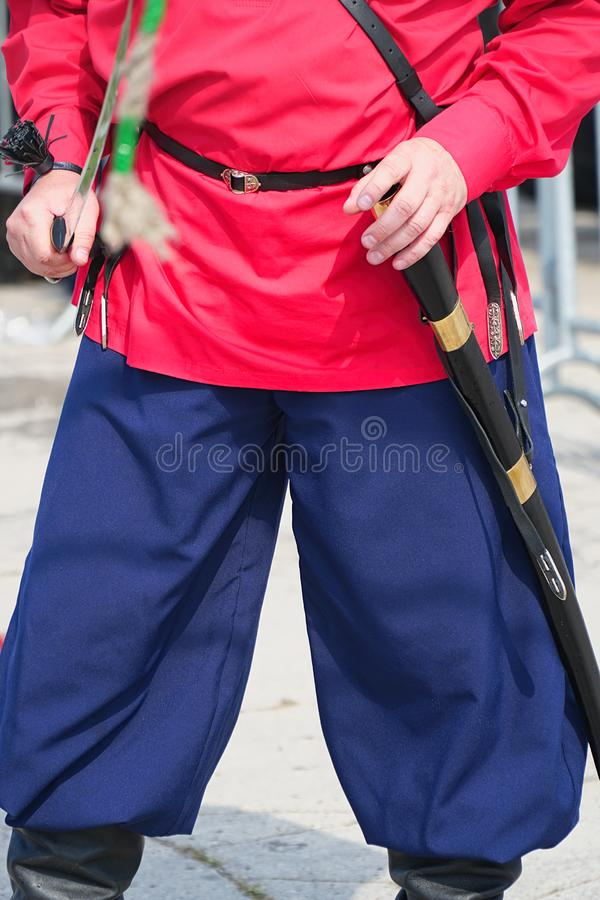Cossack in red shirt holding a cavalry saber. Cossack in a red shirt and trousers holds a cavalry checker in his hands royalty free stock image