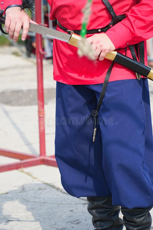 Cossack in red shirt holding a cavalry saber. Cossack in a red shirt and trousers holds a cavalry checker in his hands stock photos