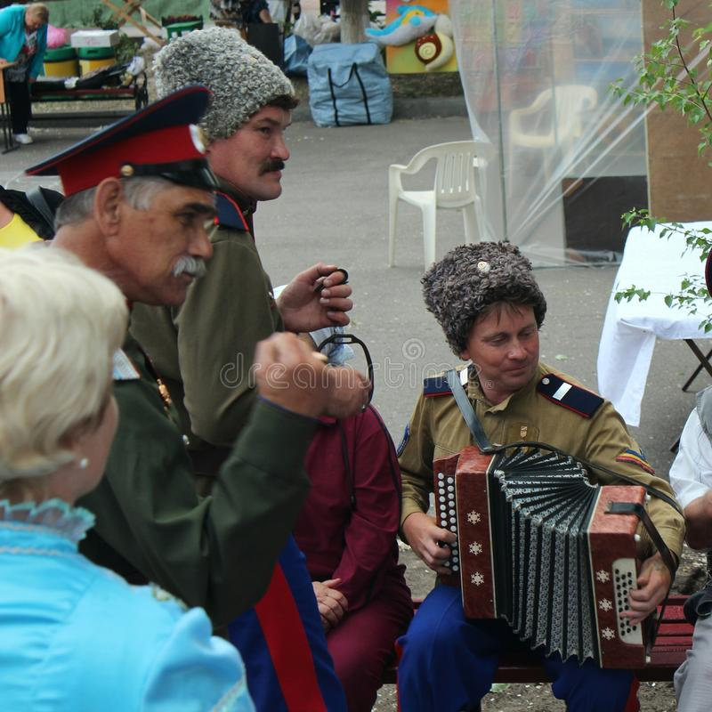 Cossack song. Cossacks sing a song to the accordion at the birthday of Mikhail Sholokhov in Vyoshenskaya, Russia royalty free stock image