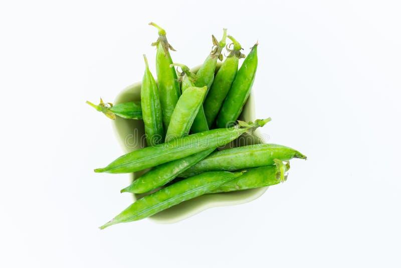 Cosse de pois fraîche verte beaucoup de légumes dans une cuvette en céramique sur un groupe blanc de fond de haricots photo stock