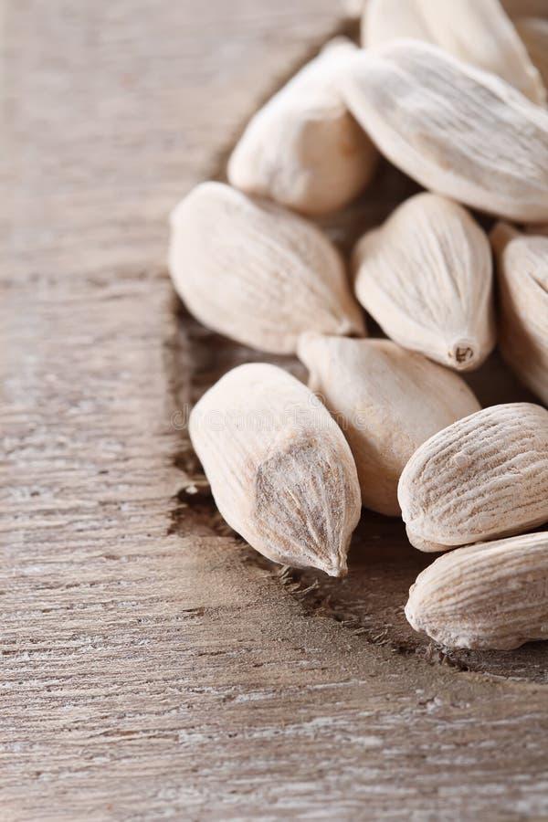 Cosses blanches de cardamome sur le vieil instruction-macro en bois photos stock