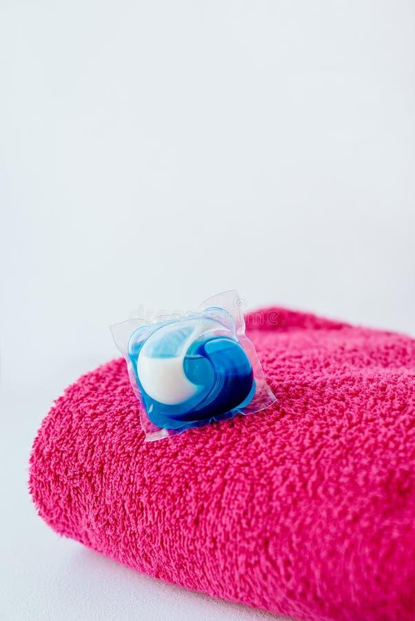 Cosses d?tersives de lavage de capsule et serviette rose photos stock