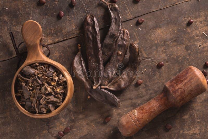 Cosses de caroube sur le bois image libre de droits