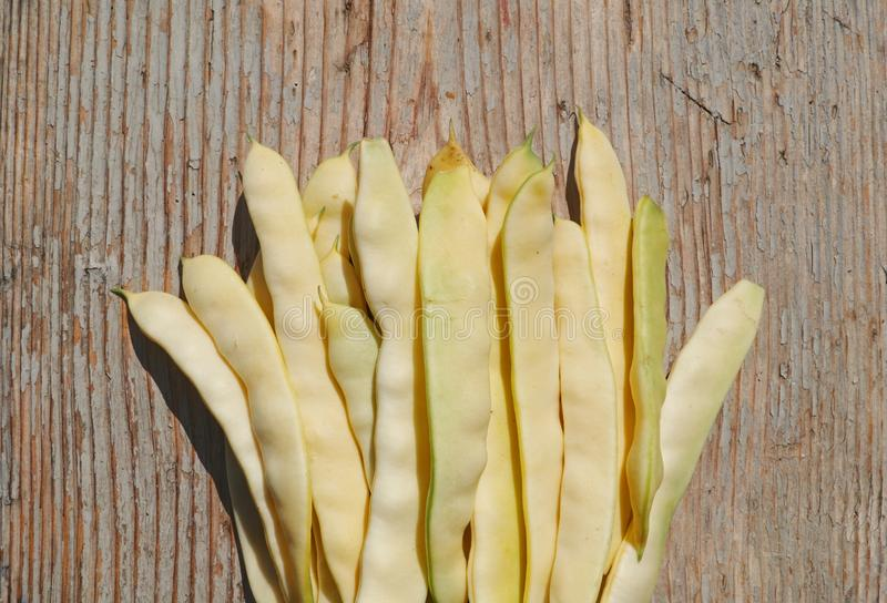 Cosses de haricot instantané jaunes sur le fond en bois rocailleux images libres de droits