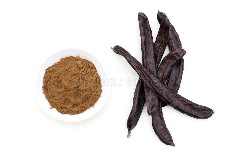 Cosses et poudre organiques mûres de fruit de caroube des haricots de sauterelle sur le fond blanc Alternative saine au cacao et  image libre de droits