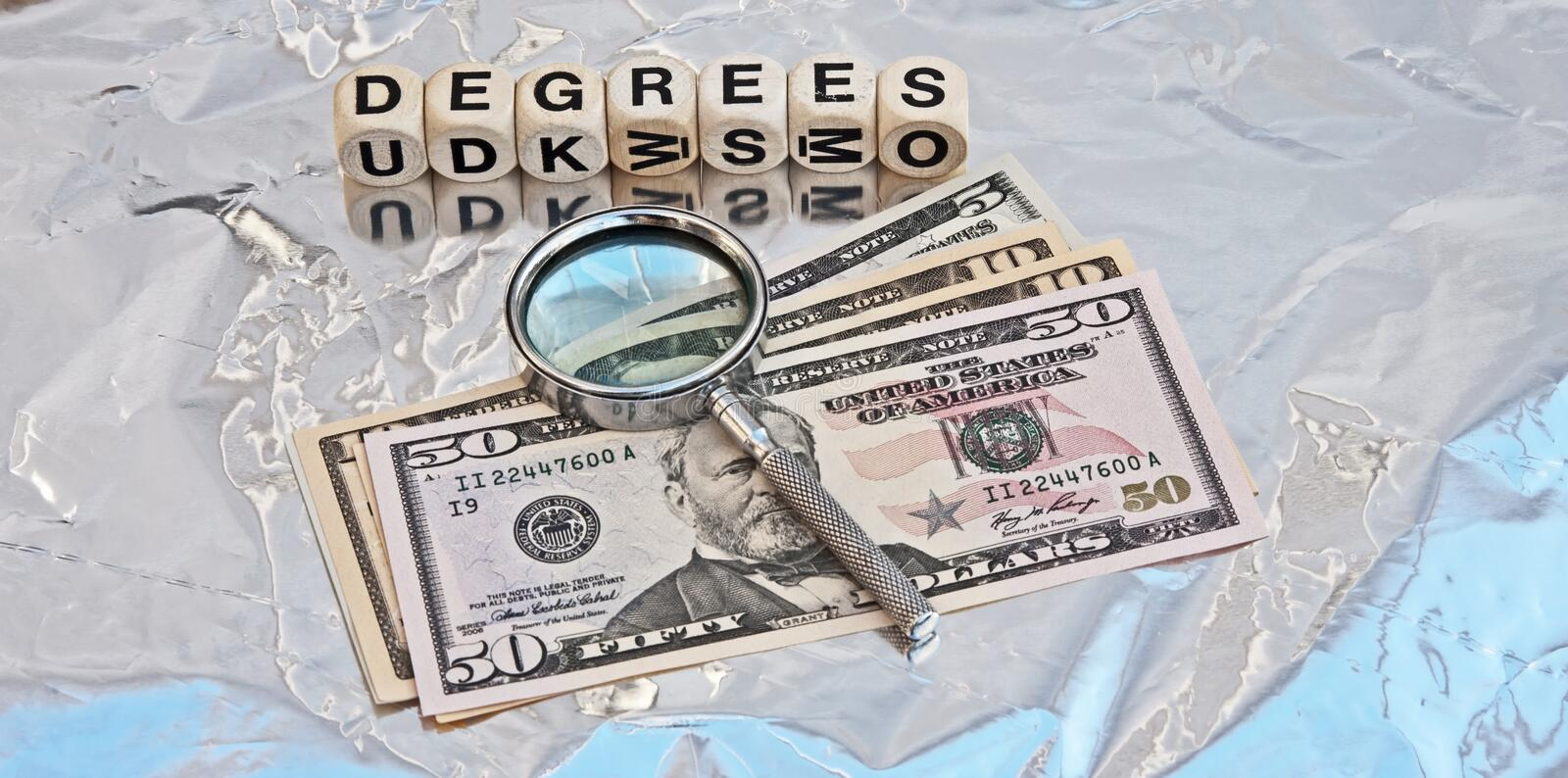 Cost of Degrees. Under scrutiny with text ' degrees ' in upper case letters on white cubes with Dollar bills and a silver magnifier stock photography