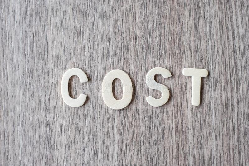 COST word of wooden alphabet letters. Business and Idea. Concept royalty free stock photos