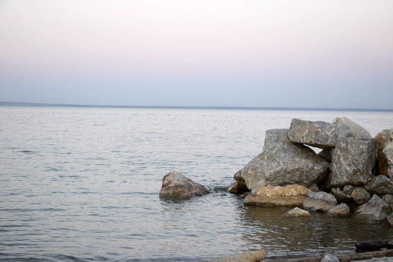 A costa arenosa do lago e dos lugares rochosos da costa, no por do sol A imagem foi tomada em uma noite morna do verão imagens de stock