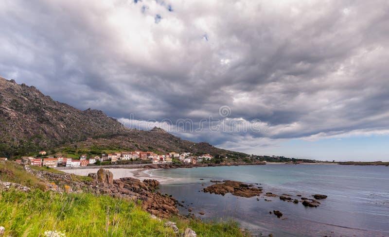 Costa atlántica de la belleza con el acantilado, la playa, el océano, el pueblo y el cielo con las nubes Galicia, Espa?a fotos de archivo