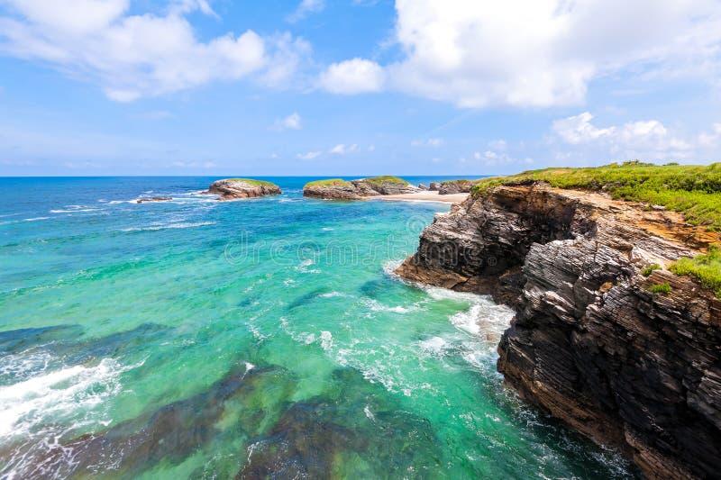 Costa atlántica de la belleza con los barcos de pesca, la playa, el océano, el pueblo, las montañas y el cielo con las nubes Gali foto de archivo libre de regalías