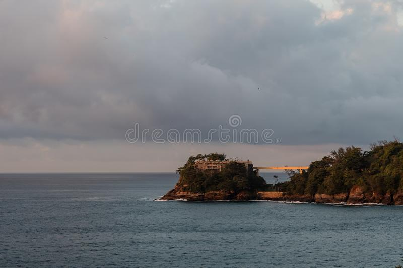 Costa Brava island, seen from Joa highway during sunrise, orange light in cloudy morning, Rio de Janeiro, brazil.  royalty free stock photography