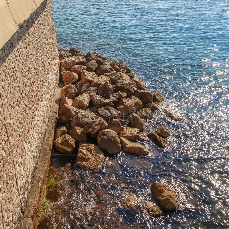 Costa con las piedras grandes que confinan el mar Mediterráneo fotos de archivo