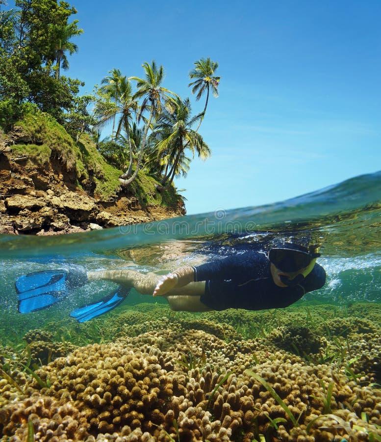 Costa da ilha sobre-sob o snorkeler no recife de corais imagem de stock