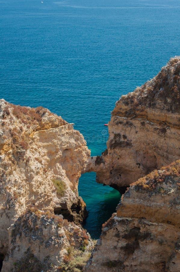 Costa de Algarve, Portugal Rocas en la línea de la playa y el agua azul fotografía de archivo libre de regalías
