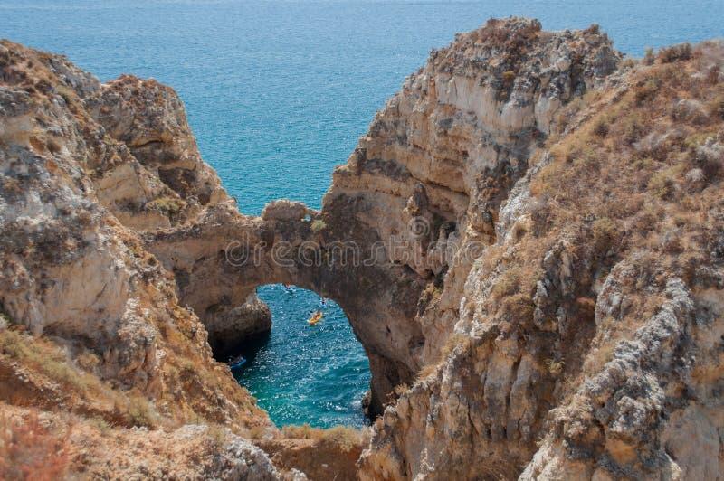 Costa de Algarve, Portugal Rocas en la línea de la playa y el agua azul imágenes de archivo libres de regalías