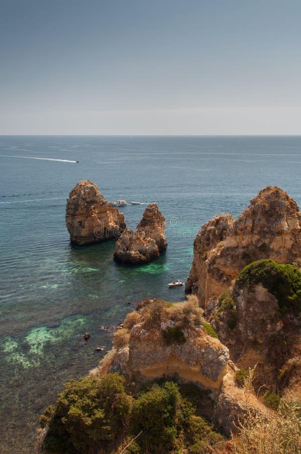 Costa de Algarve, Portugal Rocas en la línea de la playa y el agua azul foto de archivo libre de regalías