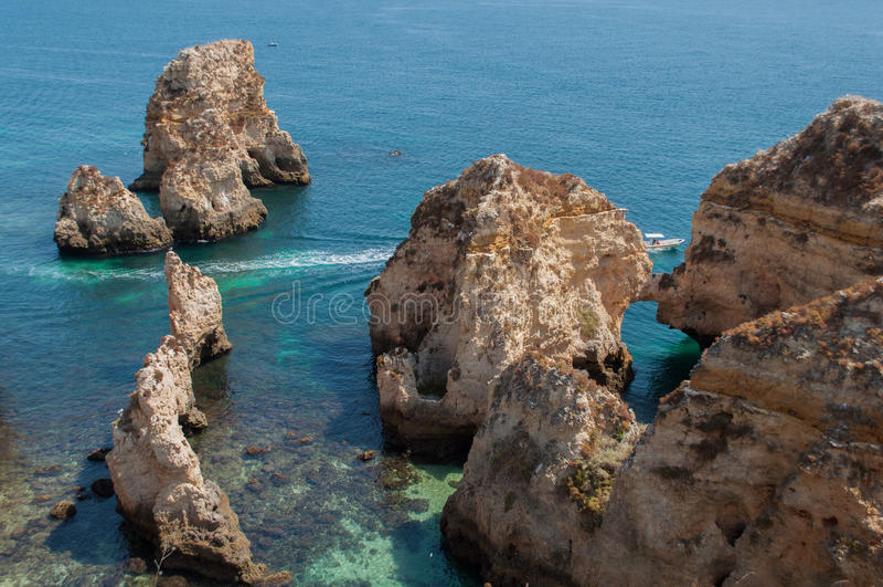 Costa de Algarve, Portugal Rocas en la línea de la playa y el agua azul fotografía de archivo