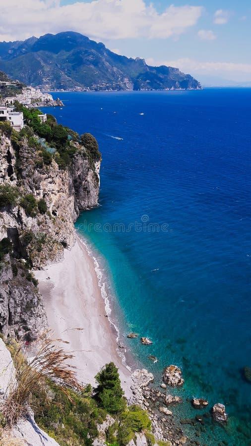 Costa de Amalfitan, playas blancas del mar azul y acantilados escarpados imagenes de archivo