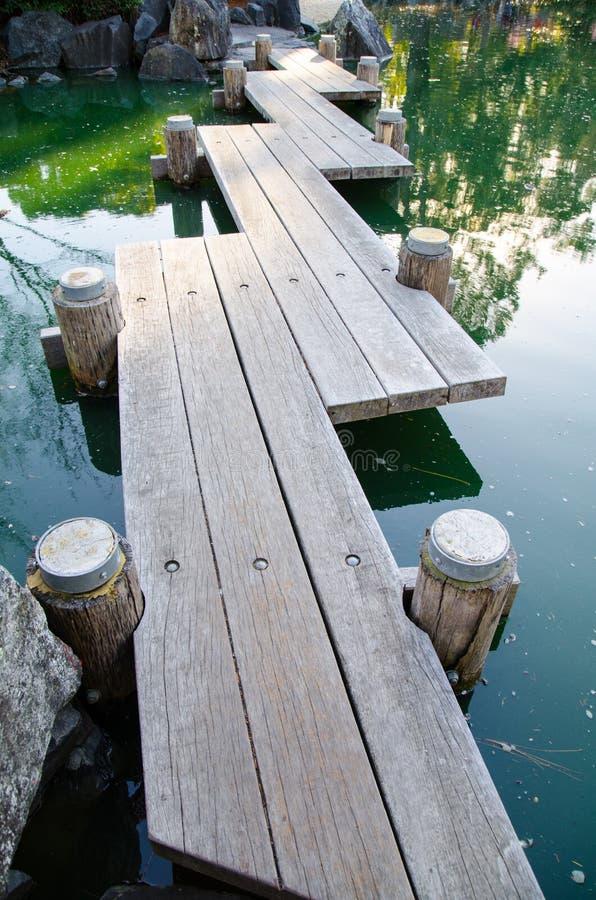 Costa de la calzada de la madera de Zig Zag que cruza una charca en el jardín foto de archivo libre de regalías