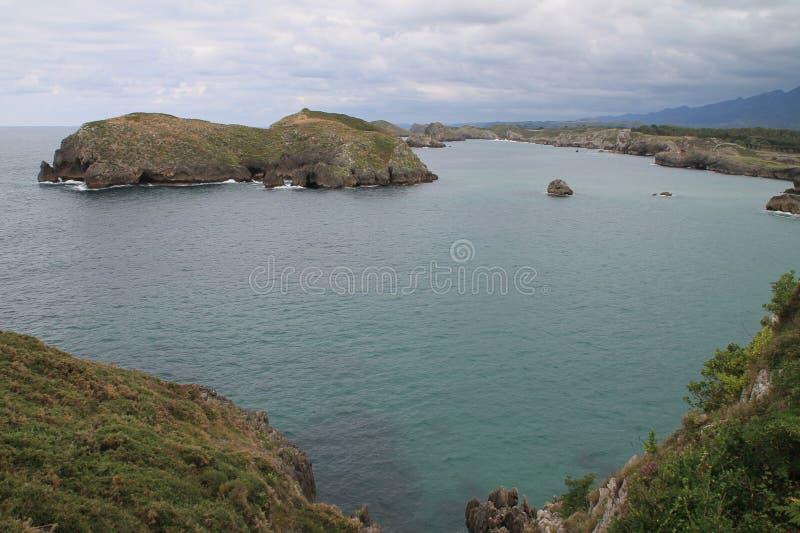 Costa de Llanes,Asturias ( Spain ). Coast of Llanes between the peninsula of Borizo and the island of Almenada, or Poo, with the island of Arnielles or royalty free stock photo