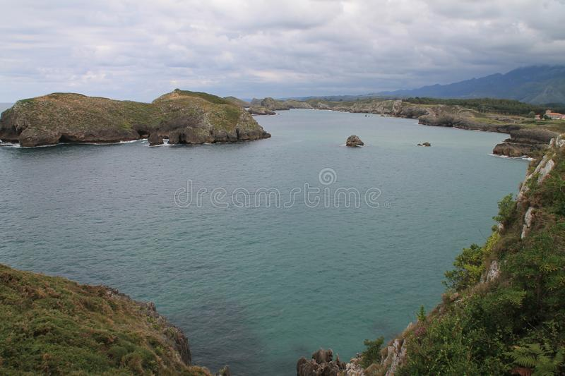 Costa de Llanes,Asturias ( Spain ). Coast of Llanes between the peninsula of Borizo and the island of Almenada, or Poo, with the island of Arnielles or royalty free stock images
