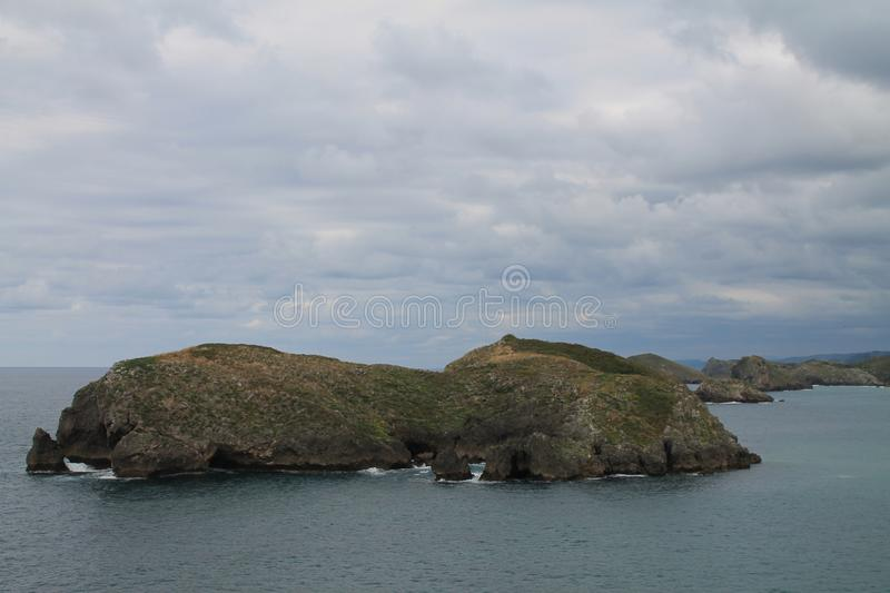 Costa de Llanes,Asturias ( Spain ). Coast of Llanes between the peninsula of Borizo and the island of Almenada, or Poo, with the island of Arnielles or stock photo