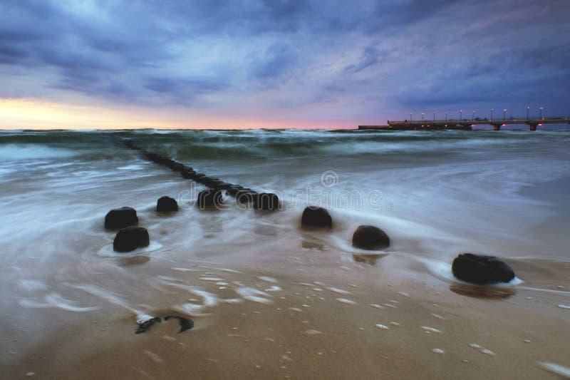 Costa de mar Báltico no por do sol, cais em Kolobrzeg, Polônia foto de stock
