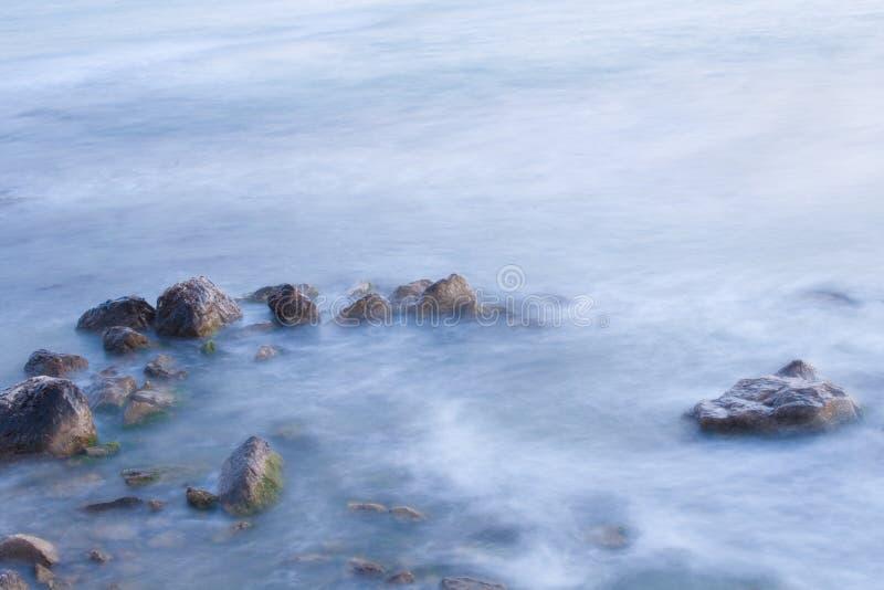 Costa de mar con las ondas en la falta de definición de movimiento. imagen de archivo