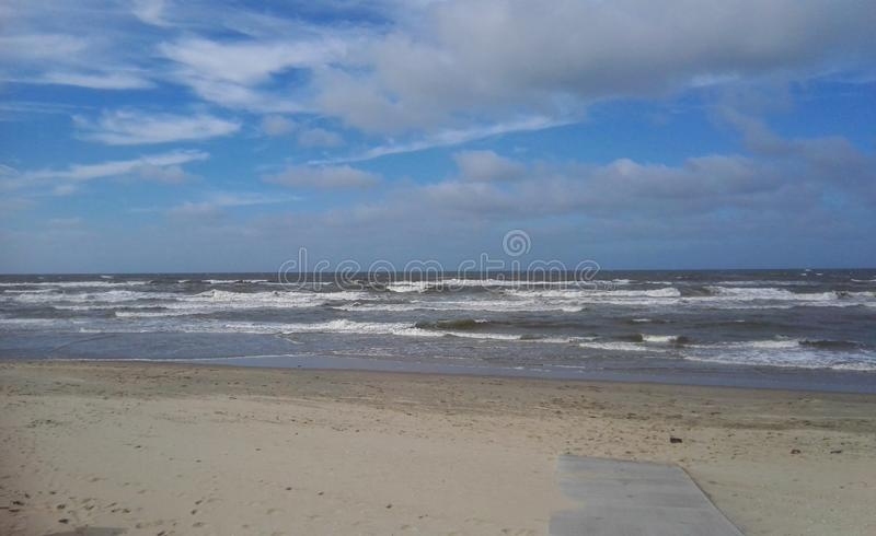Costa de Mar do Norte com um céu nebuloso e algumas ondas do mar imagem de stock
