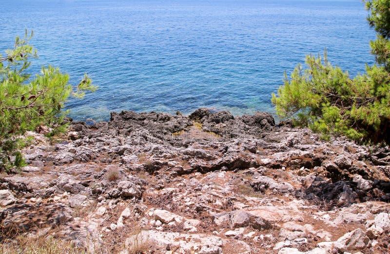 Costa de mar e praia com rochas, litoral rochoso, mar azul, bom dia ensolarado Viagem do ver?o Greece bonito A maioria de praia b fotos de stock