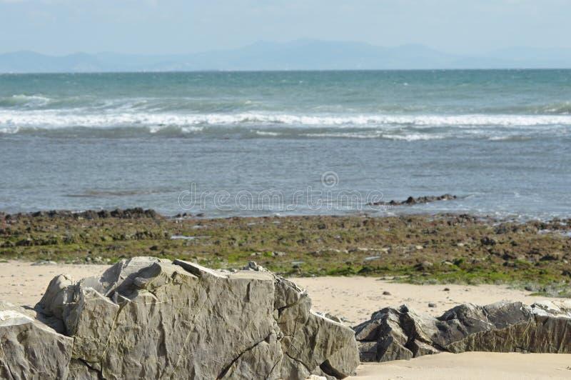 Costa de mar en Tarifa Rocas que se pegan fuera de la arena en la playa fotos de archivo