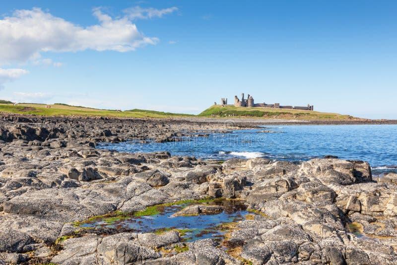 Costa de Northumberland y castillo de Dunstanburgh imagenes de archivo