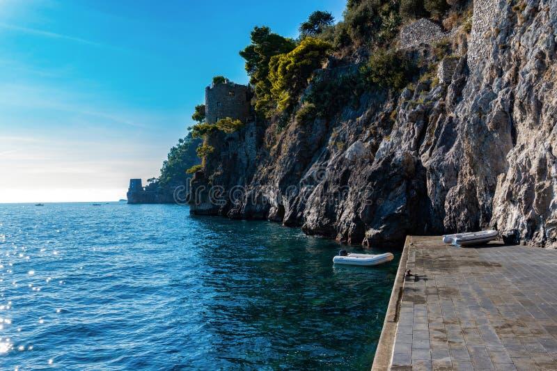 Costa di Amalfi con la riva rocciosa e barca dal pilastro in mar Mediterraneo immagine stock libera da diritti