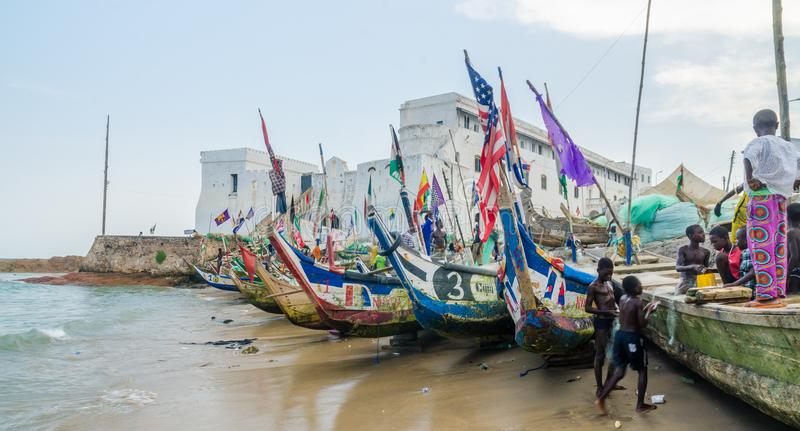 Costa do cabo, Gana - 15 de fevereiro de 2014: Os barcos de pesca de madeira amarrados coloridos no cabo africano da cidade do po fotografia de stock royalty free