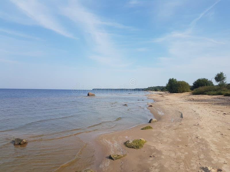 Costa do reservatório de Rybinsk com um barco na costa e um pescador da parte traseira, região de Yaroslavl, Rússia fotos de stock royalty free