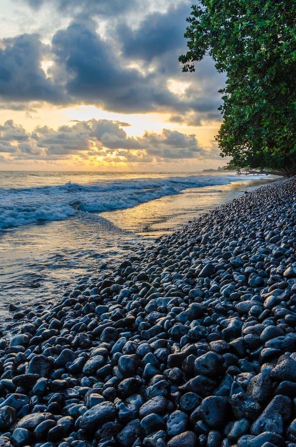 Costa dramática con la playa volcánica rocosa, el árbol verde, las ondas y la puesta del sol asombrosa, Limbe, el Camerún foto de archivo