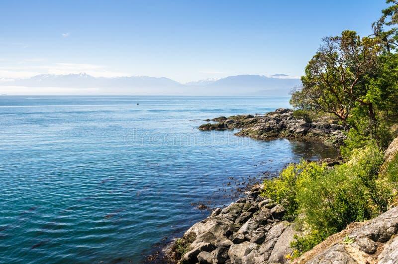 Costa e montanhas ásperas no fundo sob o céu azul foto de stock