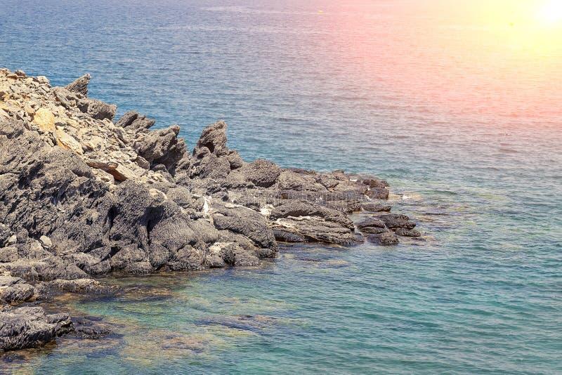 Costa fuertemente rocosa con sol y agua azul fotos de archivo libres de regalías